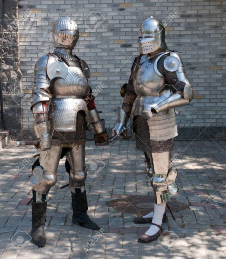 two knights in the ancient metal armor standing near the stone wall