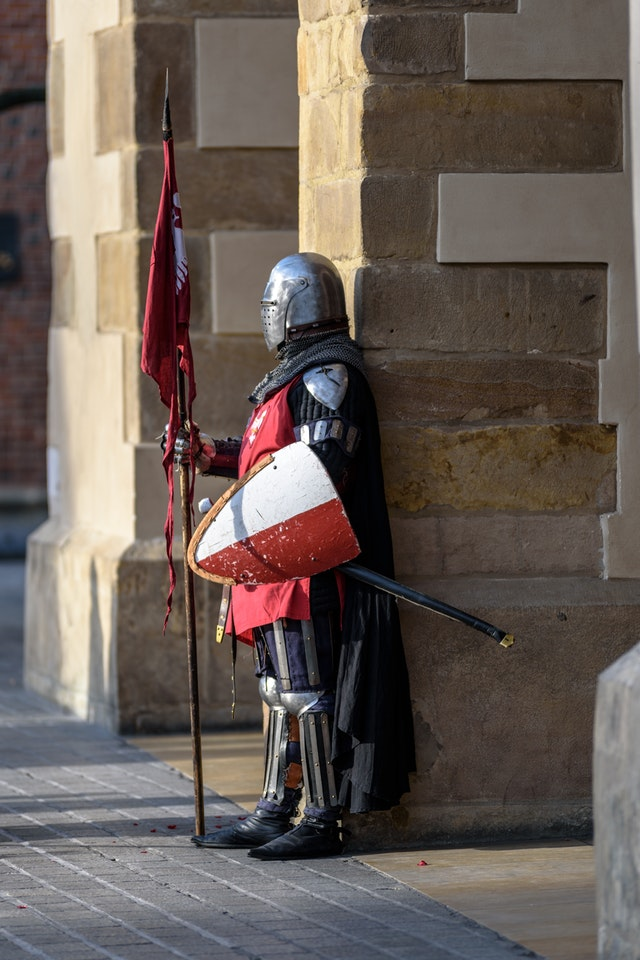 man-wearing-gray-and-red-armour-standing-on-the-streets-226746