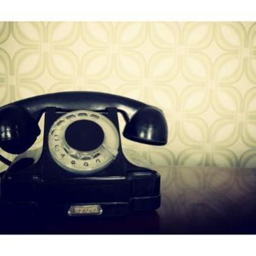 vintage-old-telephone-black-retro-phone-is-on-wooden-table-over-green-old-fashioned-wallpaper_u-l-pn07m90